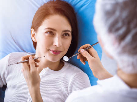 Smiling brunette woman being examined by dentist at sunny dental clinic. Hands of a doctor holding dental instruments near patients mouth. Healthy teeth and medicine concept