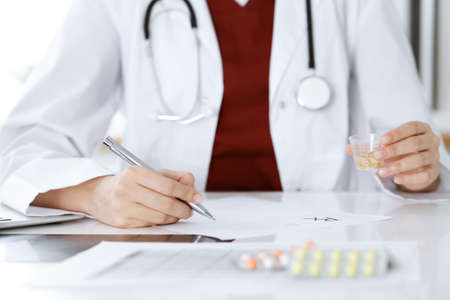 Unknown woman-doctor fills up prescription form. close-up. Panacea and life save, prescribe treatment, legal drug store. Medicine concept
