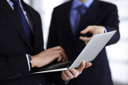 Business people use a tablet computer for discussion of their new project, standing in a modern office. Unknown businessman or male entrepreneur with a colleague at workplace. Teamwork and partnership concept.