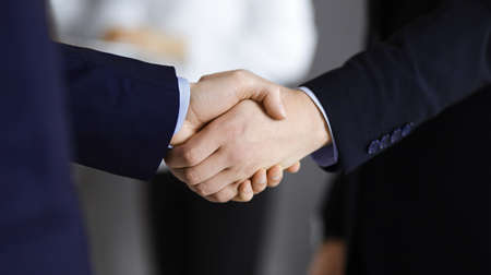Business people shaking hands at meeting or negotiation, close-up. Group of unknown businessmen and a woman stand together in a modern office. Teamwork, partnership and handshake concept