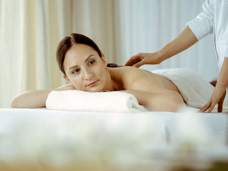Pretty brunette woman enjoying treatment with hot stones in spa salon. Beauty concept