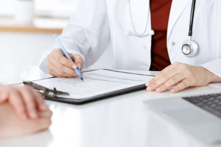 Unknown woman-doctor consulting patient and using clipboard with a medication history record. Medicine concept