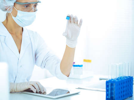 Professional female scientist in protective eyeglasses researching tube with reagents in laboratory toned in blue. Concepts of medicine and science researching