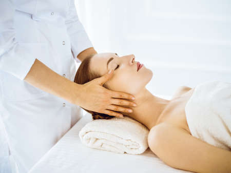 Beautiful woman enjoying facial massage with closed eyes in spa center Archivio Fotografico