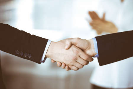 Business people shaking hands at meeting or negotiation, close-up. Group of unknown businessmen and a woman standing in a modern office. Teamwork, partnership and handshake concept