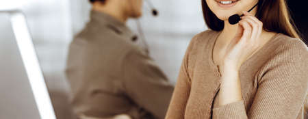 Young friendly girl in headsets is talking to a firms client, while sitting at the desk in a modern office together with her colleague. Call center operators at work