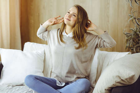 Happy brunette woman put hands behind head sitting leaned on couch, european female stretching and enjoying lazy weekend or vacation in cozy living room