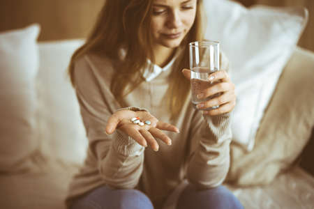 Close-up woman holding pills time to take medications, cure for headache, high blood pressure or cholesterol level remedy pain killer drugs. 스톡 콘텐츠