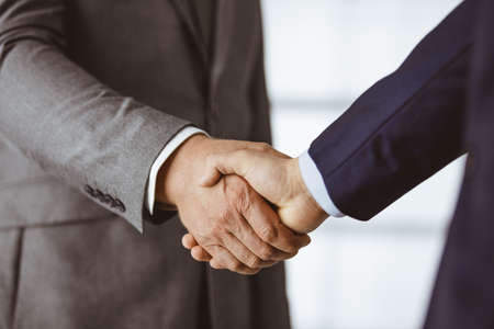 Business people in office suits standing and shaking hands, close-up. Business communication concept. Handshake and marketing Zdjęcie Seryjne