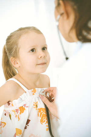 Doctor examining a child by stethoscope. Happy smiling girl patient dressed in bright color dress is at usual medical inspection 스톡 콘텐츠