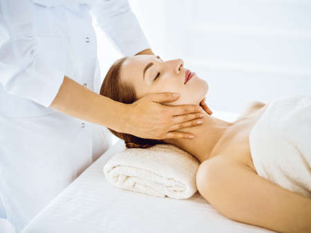 Beautiful woman enjoying facial massage with closed eyes in spa center