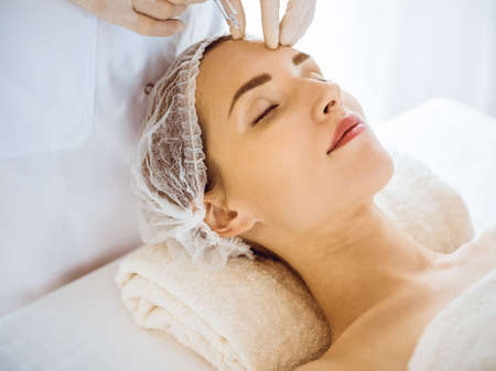 Beautiful woman receiving beauty injections with closed eyes in medical center. Beautician doctor hands doing beauty procedure to female face with syringe. Cosmetic medicine and surgery concept