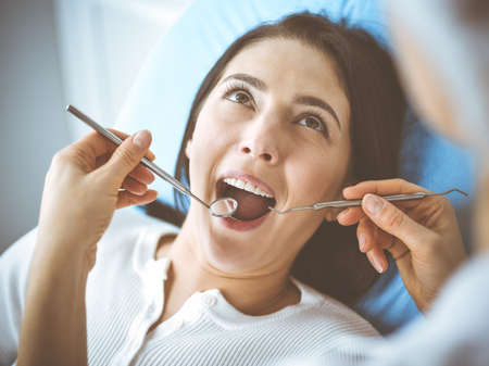 Smiling brunette woman being examined by dentist at dental clinic. Hands of a doctor holding dental instruments near patients mouth. Healthy teeth and medicine concept Zdjęcie Seryjne