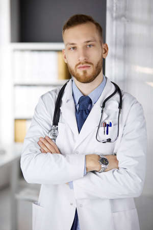 Red-bearded doctor standing straight in clinic near his working place. Portrait of physician. Medicine, healthcare
