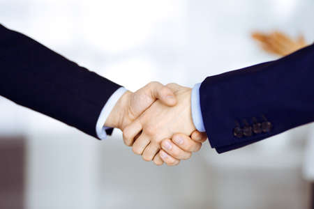 Business people shaking hands, close-up. Group of unknown businessmen standing in a modern office. Teamwork, partnership and handshake concept Banco de Imagens