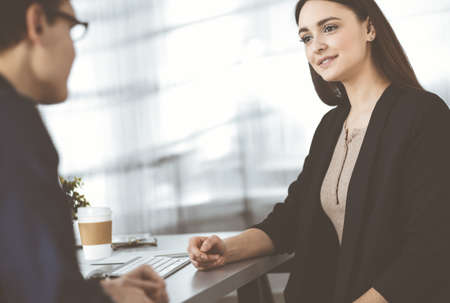 Young friendly business people are talking to each other, while sitting at the desk in a modern office. Focus on woman. Concept of business success