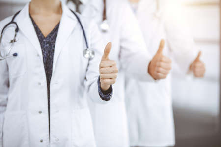 Doctors standing as a team with thumbs up in sunny clinic and ready to help patients. Medical help, insurance and medicine concept 免版税图像