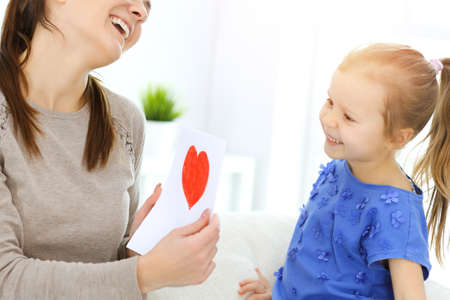 Mothers day concept. Child daughter congratulates mom and gives her postcard with red heart shape. Mum and girl happy smiling and hugging. Family fun and holiday