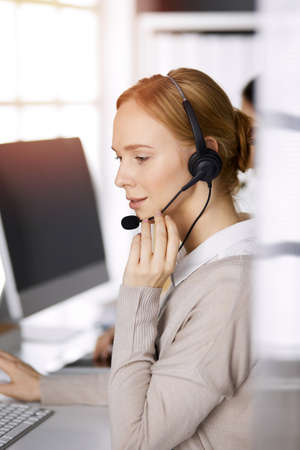Businesswoman talking by headset while sitting in sunny office. Call center and diverse people group in business Imagens