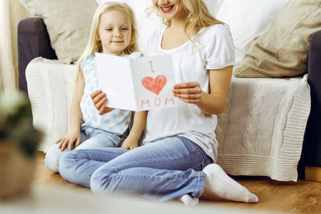 Happy mother day. Child daughter congratulates mom and gives her postcard with heart drawing. Family and childhood concepts
