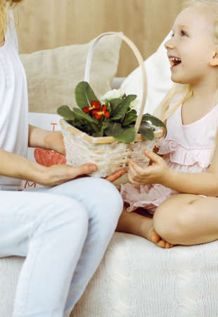 Happy mother day. Child daughter congratulates mom and gives her basket of spring flowers and postcard with heart drawing. Family and childhood concepts