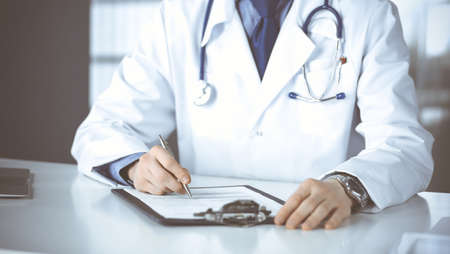 Unknown male doctor sitting and working with clipboard in clinic at his working place, close-up. Young physician at work. Perfect medical service, medicine concept