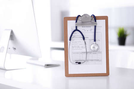 Stethoscope and clipboard with medication history records are on the table at the doctors working place. Medicine and health care concept Standard-Bild