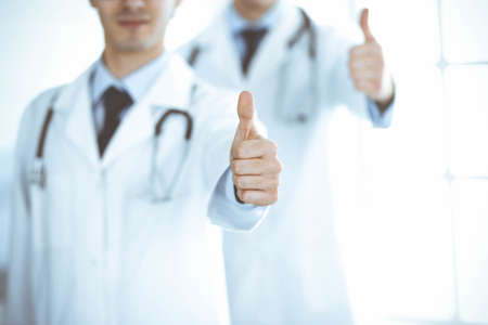 Two male doctors standing as a team and showing thumbs up as a symbol of the best service for patients in the clinic. Medicine and health care