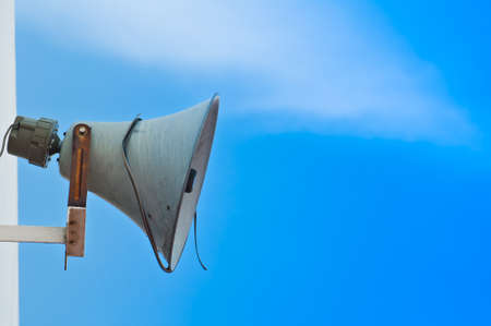 Old loudspeaker against cloudy blue sky