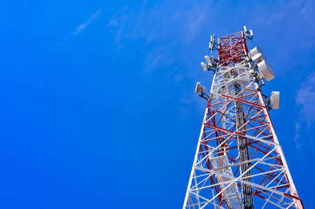 telco: Red and white tower of communications with with a lot of different antennas under clear sky