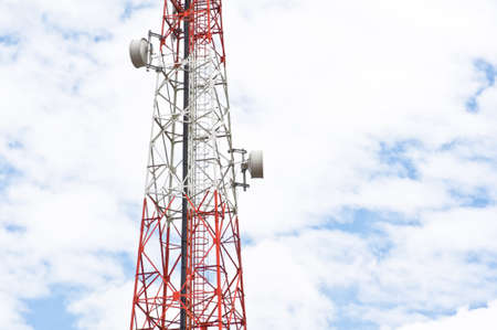Red and white tower of communications with with a lot of different antennas