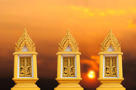 Window, door, golden Buddhist chapel in the sunset.