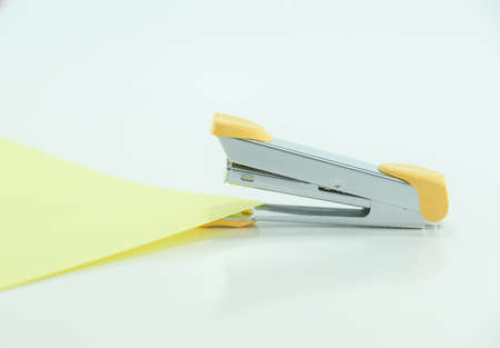 Yellow stapler and paper Stock Photo