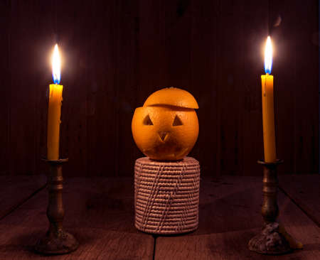 Orange Devil Halloween with candle on old wooden floor