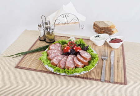 Smoked sausage with tomatoes and lettuce leaves on a plate.  Can be used in advertising and in the development of sites. Stock Photo - 99396601