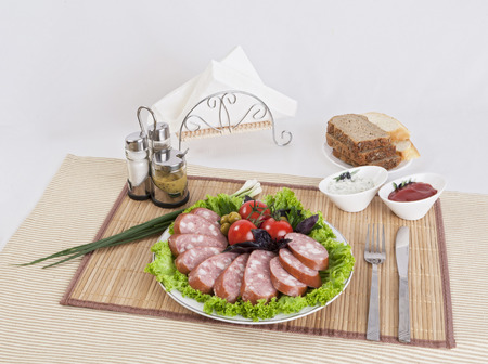 Smoked sausage with tomatoes and lettuce leaves on a plate.  Can be used in advertising and in the development of sites.