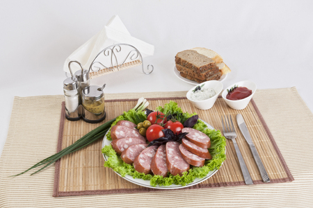 Smoked sausage with tomatoes and lettuce leaves on a plate.  Can be used in advertising and in the development of sites. Stock Photo - 101742056
