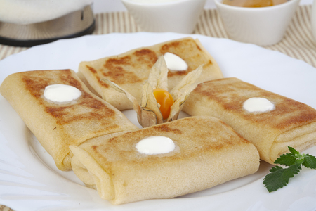 Pancakes with cottage cheese for tea with honey, sour cream and lemon. The perfect beginning of the morning with a light, delicious breakfast. Fried with golden crust. A cup of fresh morning tea.