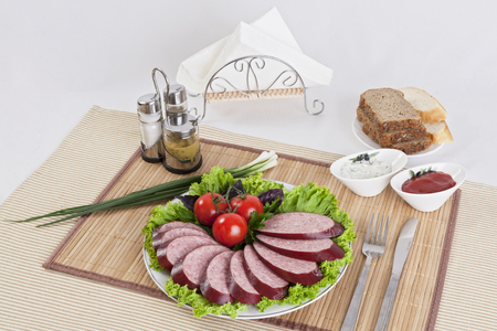 Smoked sausage with tomatoes and lettuce leaves on a plate.  Can be used in advertising and in the development of sites. Stock Photo - 101742144