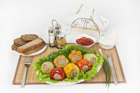Bulgarian pepper stuffed with meat with herbs, sauce and sour cream. A fine dish for a hearty healthy dinner. Serve hot with black or white bread. Mustard is a good seasoning for the dish. Фото со стока