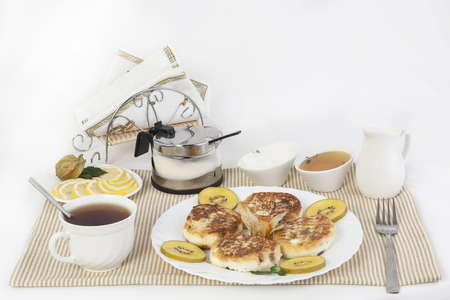 Ñurd pancakes to tea with honey and sour cream. This is a good treat for tea with lemons. A good and healthy breakfast that gives strength and cheerfulness. Stock Photo