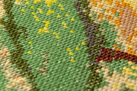 Cross-stitch. Macro photography of embroidery sites. Shooting with a small bluff of sharpness. Bright patterns on the canvas. Stock Photo