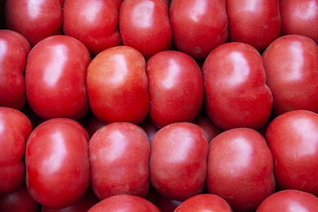 Heap of fresh ripe red tomatoes without branches close up. Vegetable for salads, pizza, sauces, salsa, ketchup. Top view. Stock Photo