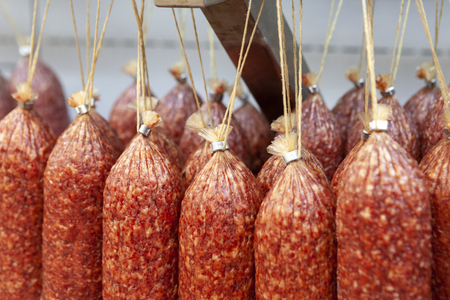 Hanging sticks of uncooked smoked sausage. Macro photo of salami. Shallow deep of field. Front view.