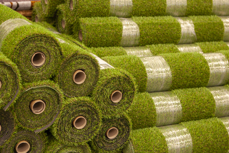 Rolls artificial grass in store of building materials. Cover for lawn, football and golf field. Soft plastic grass. Close up. Foto de archivo - 105315168