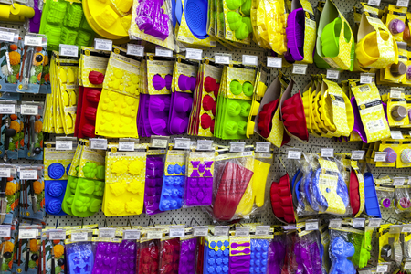 TOLYATTI, RUSSIA, JULY 08, 2018: Store stand with colorful silicone baking equipment. Forms for baking pies, cakes, cookies, cupcackes, making sweets, candies. Homemade baking. Front view.