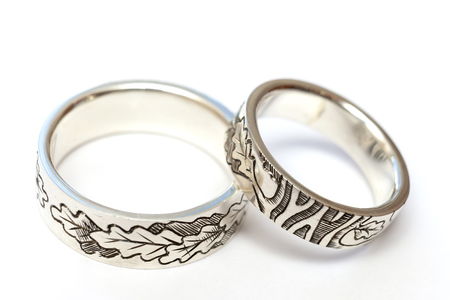 Silver engagement rings with engraving according to the authors sketch. A photo on a white background, isolate.