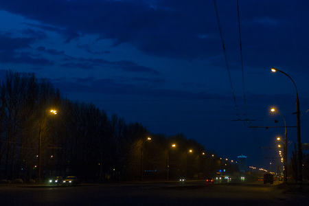 Night city in the rays of city lights with road, cars, electrical cable and trees. Dark sky with clouds.