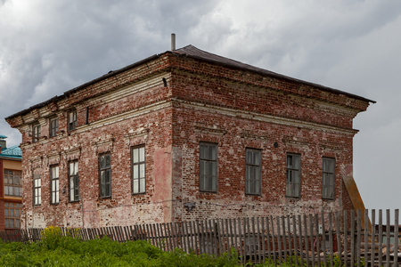 Old brick house behind a wooden sagging fence. Old building under gray sky with clouds. House covered with salt deposits.