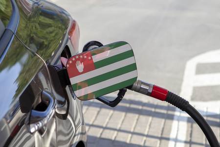 Flag of Abkhazia  on the car's fuel tank filler flap. Fueling car with petrol pump at a gas station. Petrol station. Gasoline and oil products. Close up.